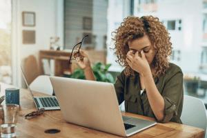 woman rubbing eyes after staring at computer