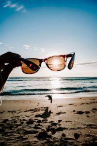 holding glasses up to the sun on a beach