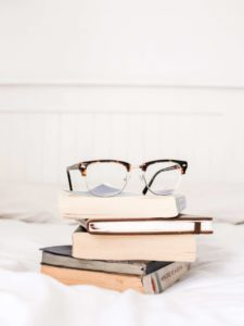 glasses resting on top of stack of books