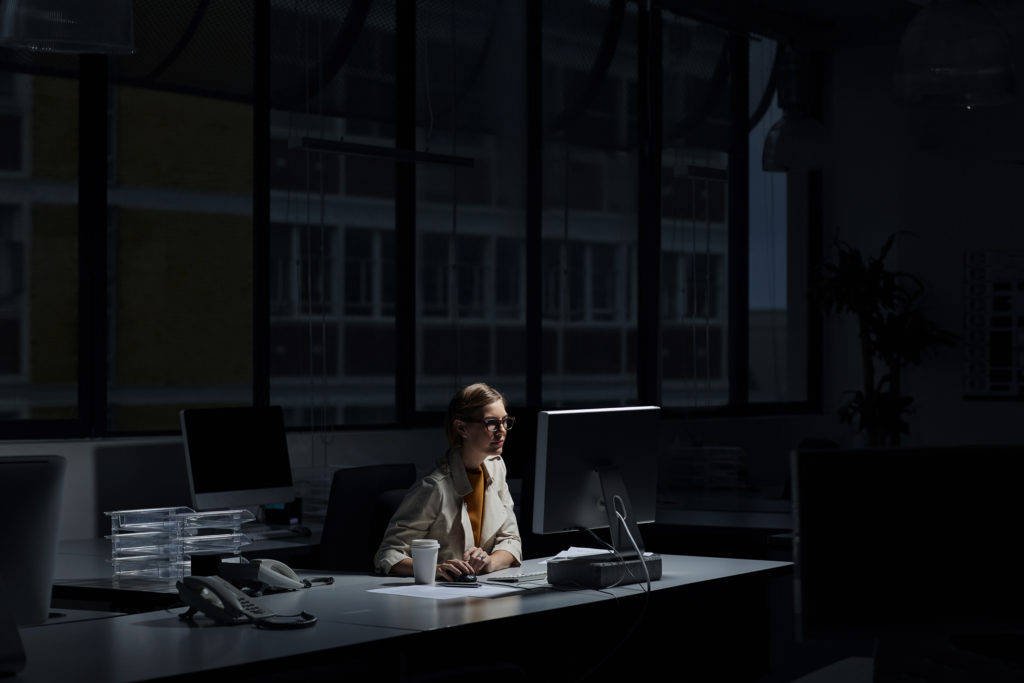 Young businesswoman using computer in dark office