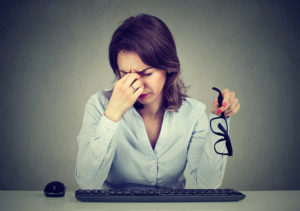 Woman with glasses suffering from eyestrain after long hours working on computer