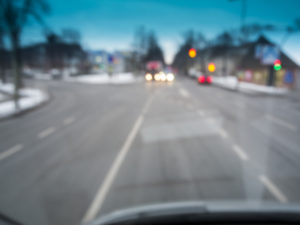 Blurred view through the windscreen of a vehicle on public road traffic at dawn.