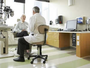 An opthamologist is listening to the patient in an exam room.
