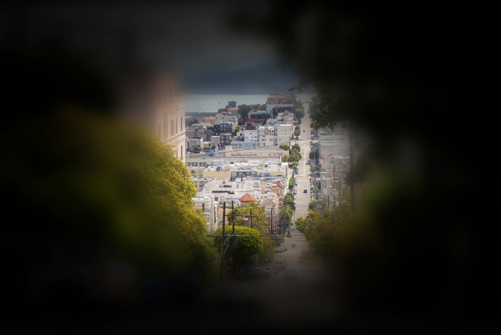 Seeing from the perspective of a patient with tunnel vision. The side vision is blurry while in the centre a  clear view of a town with building can be seen.