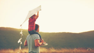 man and daughter holding kite