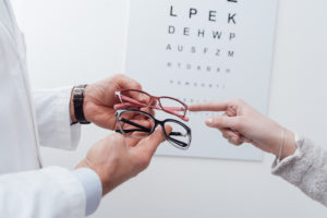 woman receiving glasses in front of eye exam