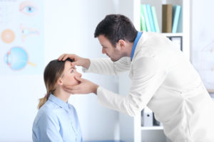 eye doctor examining woman's eye