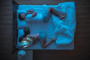 woman looking at smartphone in bed